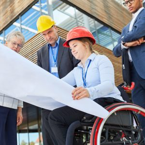 Disabled woman as an architect in a wheelchair with blueprint together with engineers
