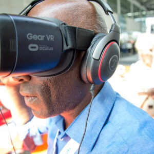 Close-up of man wearing VR headset, with blurred background of a tradeshow