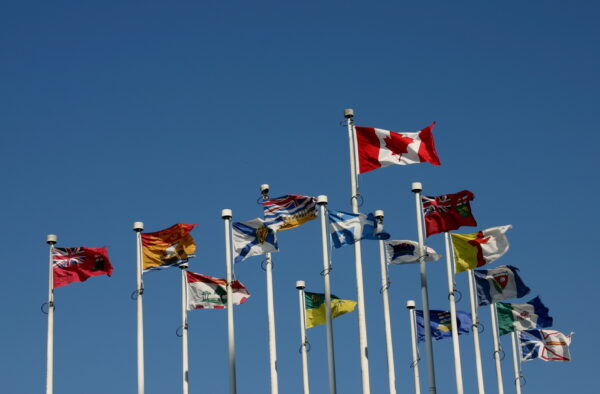 The Canadian flag and provincial flags blowing in the wind, against a clear blue sky